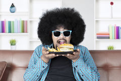Hungry Afro man eats cheeseburger. Portrait of hungry Afro man holding a plate of cheeseburger and french fries while wearing sunglasses at home Stock Image