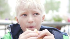 Hungry albino boy eating a hamburger on the street stock video footage