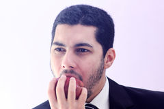 Hungry arab business man eating red apple Royalty Free Stock Photo