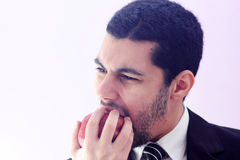 Hungry arab business man eating red apple Royalty Free Stock Photos