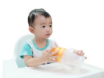 Hungry Asian baby in the highchair. Kid waiting for food, isolat Royalty Free Stock Photography