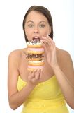Hungry Attractive Young Woman Holding a Pile of Iced Donuts Royalty Free Stock Images
