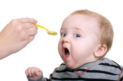 Hungry Baby Boy. Cute baby being feed rice cereal with a yellow spoon Royalty Free Stock Image
