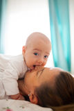 Hungry baby boy. Cute baby boy is biting his mother's nose Stock Photography