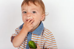 Hungry baby boy eating cucumber Stock Photo