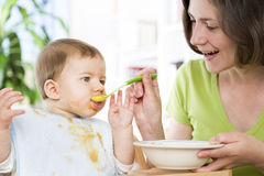 Hungry baby boy eating food next to his mother. Stock Photography