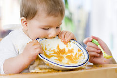 Hungry baby boy eating food next to his mother. Royalty Free Stock Image