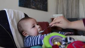 Hungry baby cant wait for food. Mother is teasing baby but giving him to eat with spoon.  stock footage
