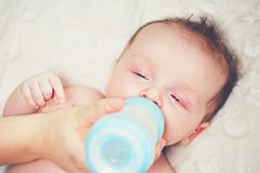 Hungry baby drinking milk Stock Photography