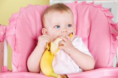 Hungry baby eating fruit Stock Photography