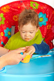 Hungry baby eating puree. And sitting on chair Stock Photos
