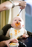 Hungry baby eating solid food from a spoon. Hungry six month old baby eating solid food from a spoon Stock Images