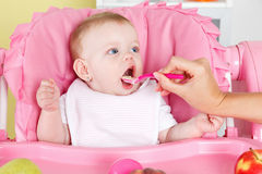 Hungry baby girl is feeded by mother Royalty Free Stock Image