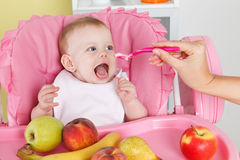 Hungry baby girl is feeded by mother Royalty Free Stock Photos