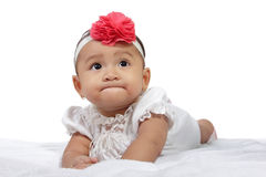 Hungry baby gulp. Hungry little baby girl in bed looking up, isolated on white background Royalty Free Stock Photos