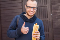 Hungry bearded customer eating delicious fast food: hotdog. Outs Stock Photos