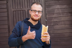 Hungry bearded customer eating delicious fast food: hotdog. Outs Royalty Free Stock Photography