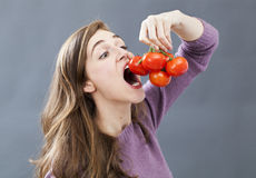 Hungry beautiful girl eating up tomatoes with appetite and greed Royalty Free Stock Photos