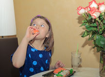 Hungry beautiful little girl looking up and eating Stock Photos