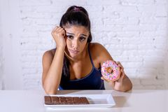 Pretty latin woman looking at chocolate and donuts tired of diet restrictions stock image