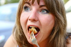 Hungry blond girl eating a piece of pizza Stock Photos