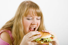 Hungry blonde and hamburger Royalty Free Stock Photography