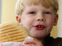 Hungry boy. Boy eating toasted bread Stock Images