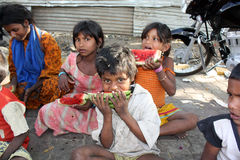 Hungry Boy. A poor and hungry Indian boy eating a watermelon, his family sitting in the background Stock Image