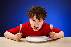 Hungry boy. On blue background stock photos