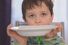 Hungry boy with beautiful eyes waiting for dinner. Holding empty plate in his hands stock photography