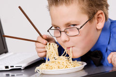 Hungry boy eating chinese noodles with sticks royalty free stock images