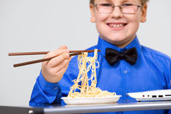 Hungry boy eating chinese noodles with sticks Royalty Free Stock Photography