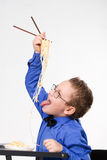 Hungry Boy Eating Chinese Noodles With Sticks Royalty Free Stock Photo