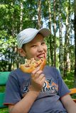 Hungry boy eating pizza. Outdoor Stock Images