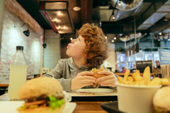 Hungry boy eats burger in restaurant. Hungry caucasian redhead boy eats burger in the restaurant Royalty Free Stock Photo