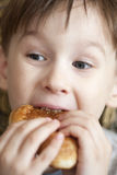 Hungry boy eats with opened mouth. Big cookie Stock Photos