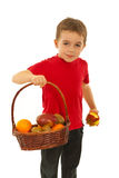 Hungry boy with fruits in basket Stock Images