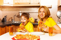 Hungry boy and his mother eating pizza in kitchen Royalty Free Stock Photos