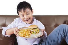 Hungry boy holds junk food Stock Photo