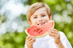 Boy at a party is eating a delicious watermelon Royalty Free Stock Image