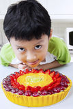 Hungry boy with a strawberry pie. Photo of cute little boy looks hungry with a strawberry pie in the kitchen at home Stock Photography