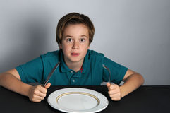 Hungry boy. Wairing for food royalty free stock photography