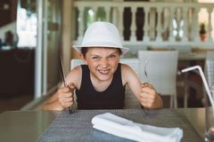 Hungry boy waiting for dinner in restaurant. Stock Photos