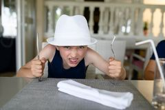 Hungry boy waiting for dinner in restaurant. Royalty Free Stock Photo