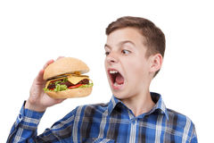 Hungry boy wants to eat a big hamburger Stock Image