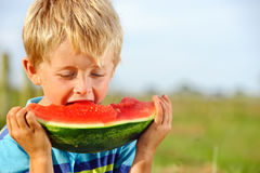 Hungry boy with watermelon outdoors Royalty Free Stock Photography