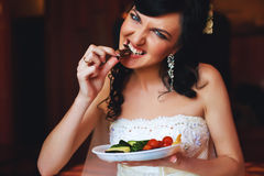 Hungry bride eating from plate Royalty Free Stock Images