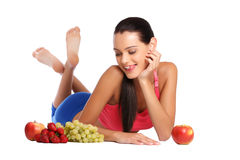 Hungry brunette teenager with healthy fruits. Nice young woman lying on the floor with healthy fruits Stock Photos