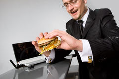 Hungry businessman eating hamburger Stock Images