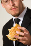 Hungry businessman eating hamburger Royalty Free Stock Photography